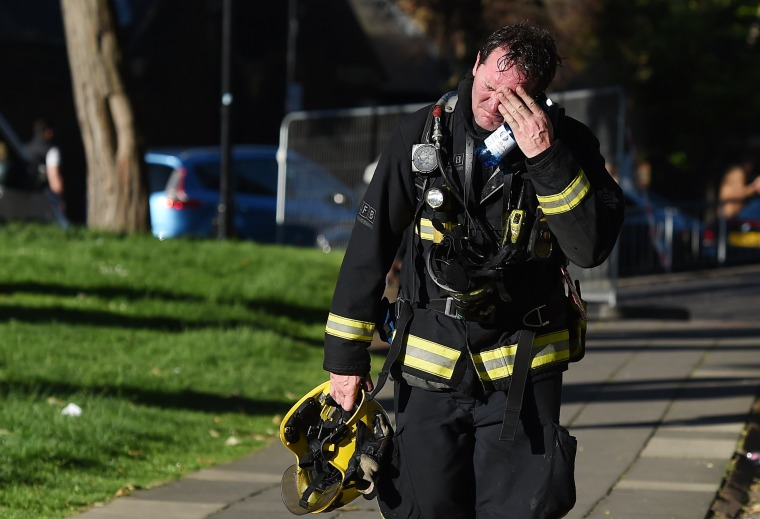 Image: A firemen reacts after battling a huge fire at the Grenfell Tower