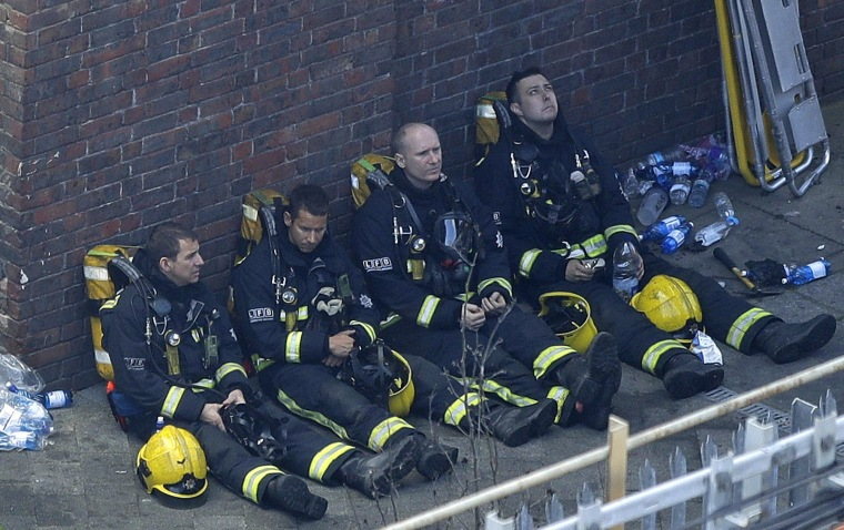 Image: Firefighters rest as they take a break in battling a massive fire that raged in a 27-floor high-rise apartment building in London