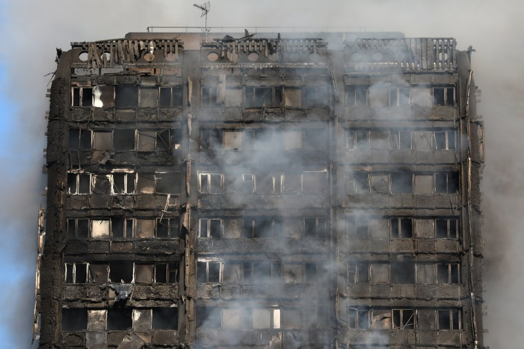 Image: Smoke billows from a tower block severly damaged by a serious fire, in north Kensington, West London