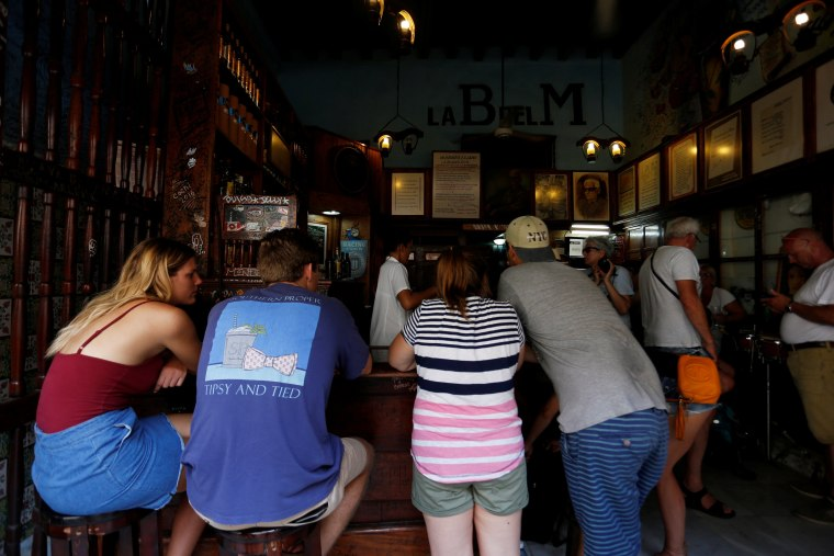 Image: People have drinks at a bar in Havana