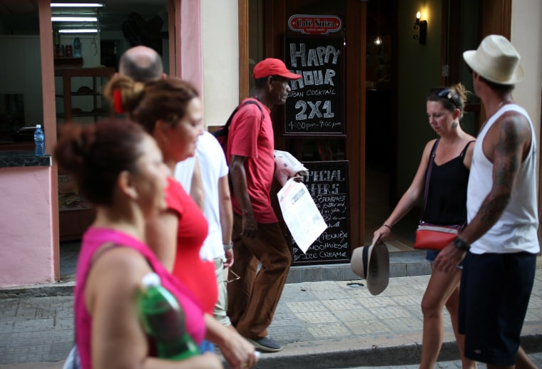 """Image: People walk past a bar and a sign advertising """"Happy hour"""" in Havana"""