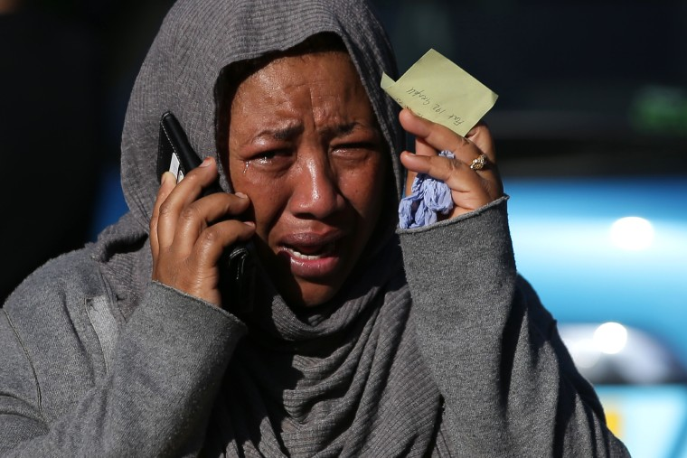 Image: A woman cries as she tries to locate a missing relative
