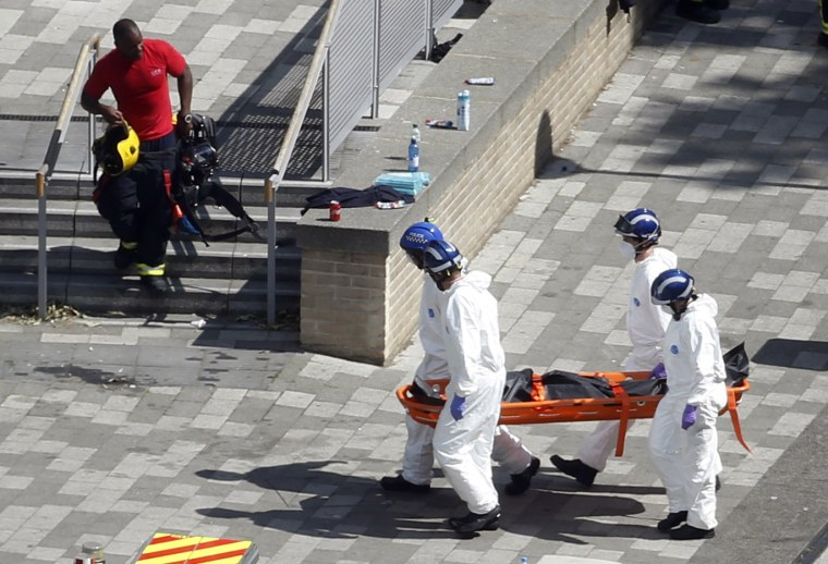 Image: Members of the forensic team move a body near the scene of the fire