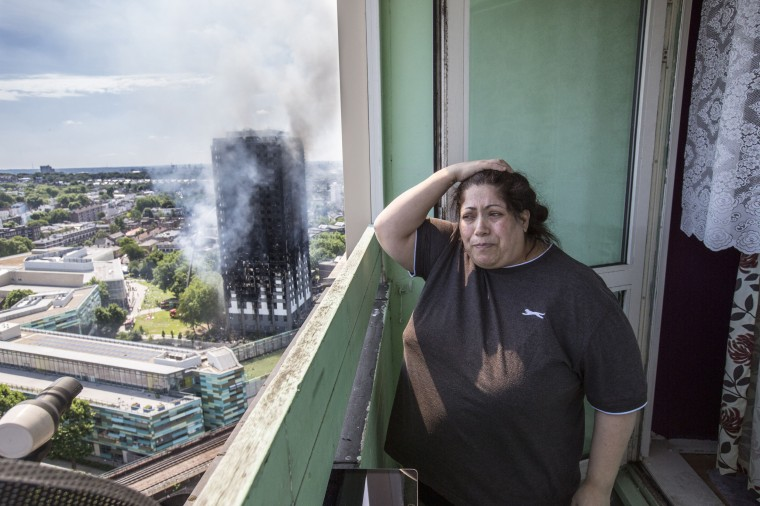 Image: Local resident Georgina stands distraught on her balcony as she watches the fire engulf the tower from a distance