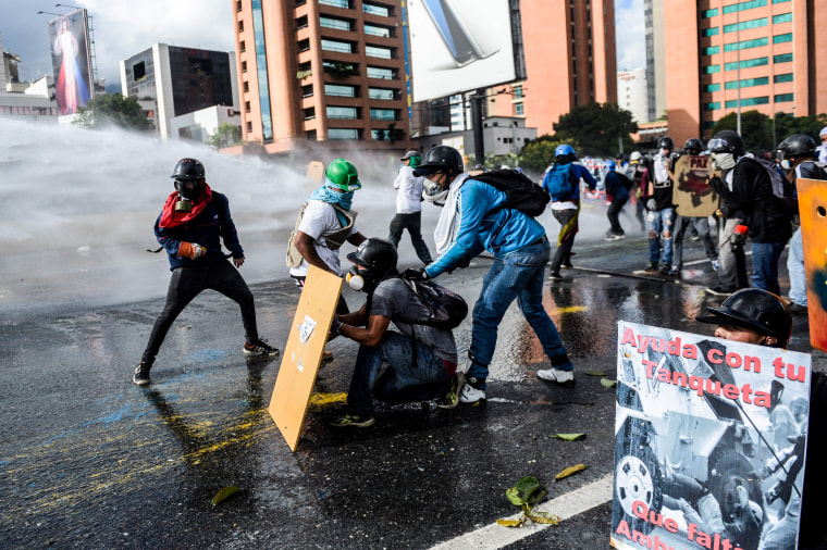 """Image: Opposition activists use makeshift shields as they clash with the police during the """"Towards Victory"""" protest against the government of President Nicolas Maduro in Caracas on June 10, 2017."""