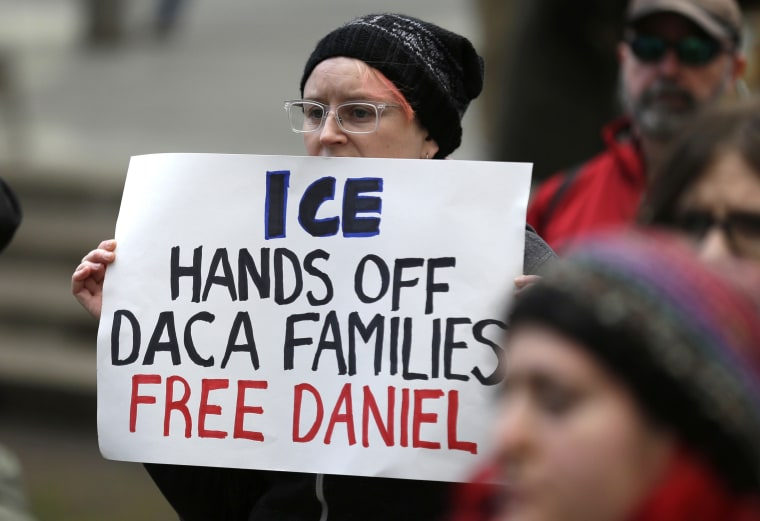 """FILE - In this Feb. 17, 2017 file photo, a protester holds a sign that reads """"ICE Hands Off DACA Families Free Daniel,"""" during a demonstration in front of the federal courthouse in Seattle."""