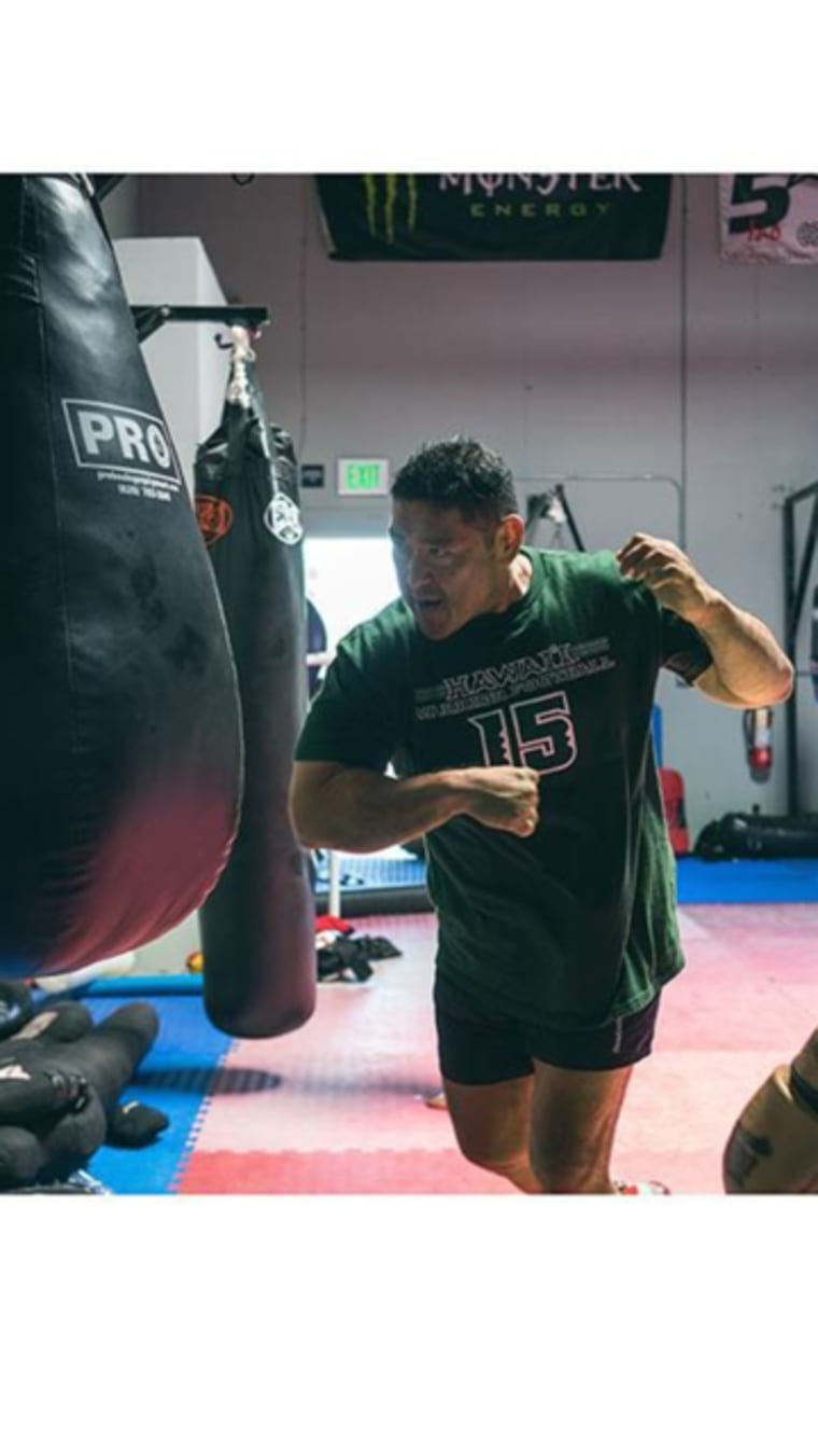 Colin Oyama, head coach at his Team Oyama MMA training center, practicing with a bag.