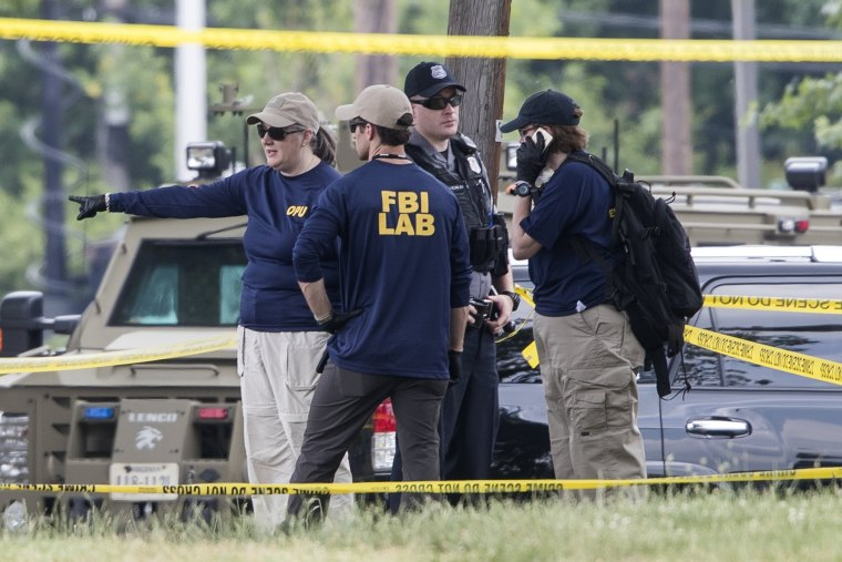 Image: FBI employees and other law enforcement work outside the Eugene Simpson Stadium Park