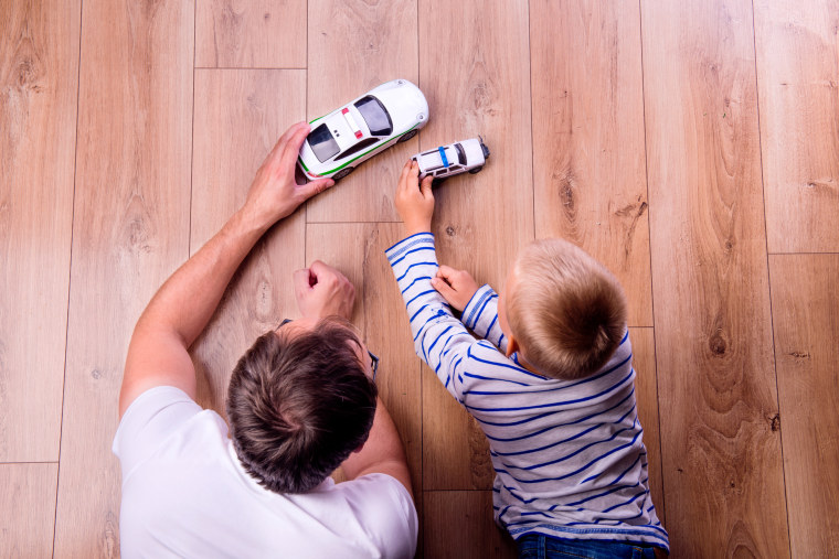 Image: A father with his son playing with cars.