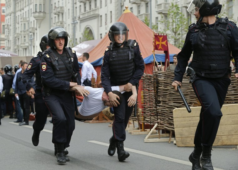 Image: Russian police officers carry a detained participant of an unauthorized opposition rally