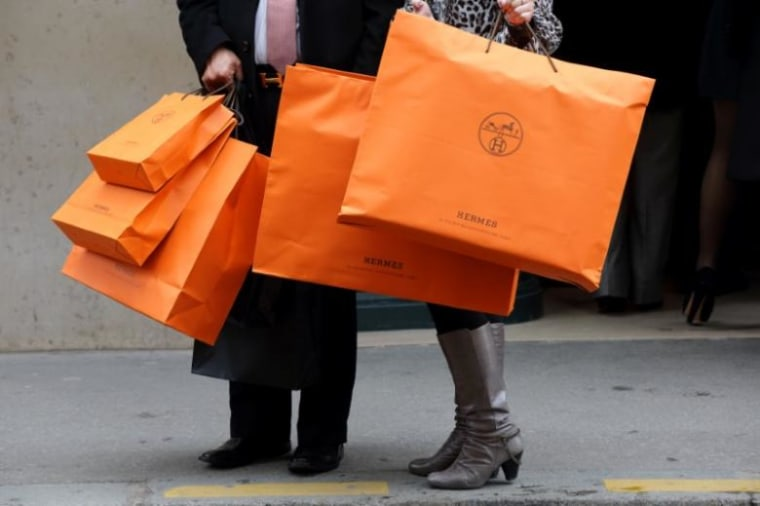A couple walk with Hermes shopping bags as they leave a Hermes store in Paris