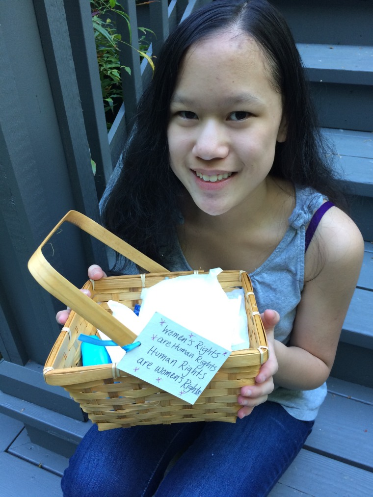 """Cordelia Longo sitting on the steps, holding one of the baskets she made with the tag """"Women's Rights are Human Rights. Human Rights are Women's Rights."""" Cordelia Longo says she sees Hillary Clinton as a role model."""