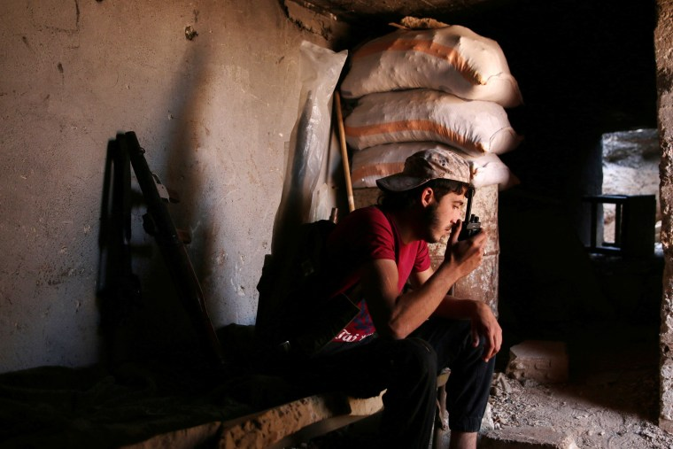 Image: A Free Syrian Army fighter speaks on radio at al-Nuaimah village in Deraa province