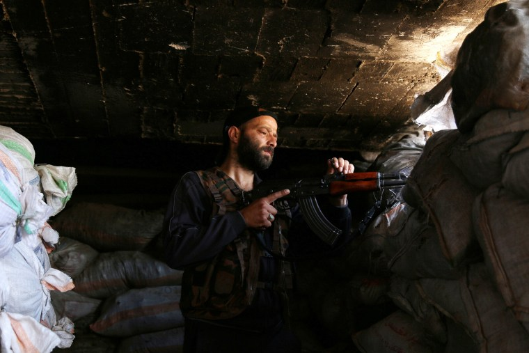 Image: A Free Syrian Army fighter stands in his position  at al-Nuaimah village in Deraa province