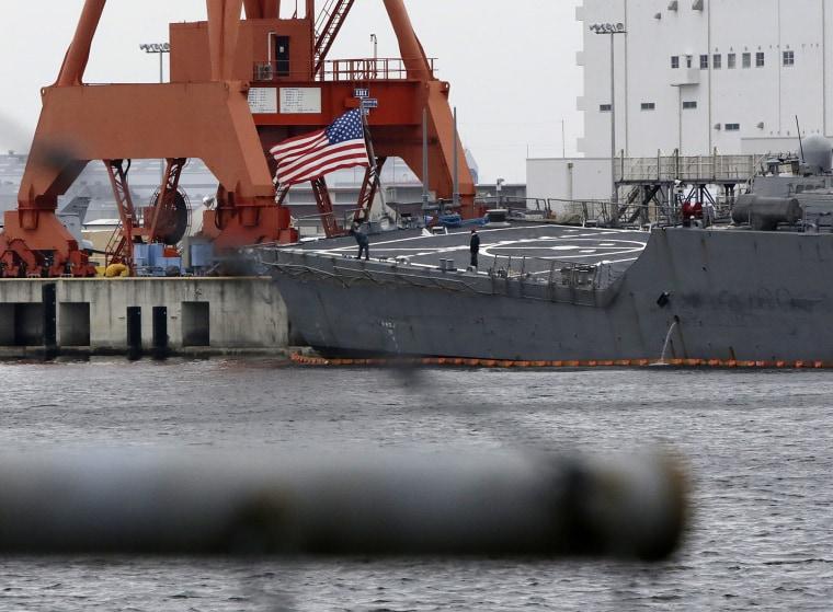 Staffs stand near the U.S flag of damaged USS Fitzgerald seen at the U.S. Naval base in Yokosuka, southwest of Tokyo Sunday, June 18, 2017.