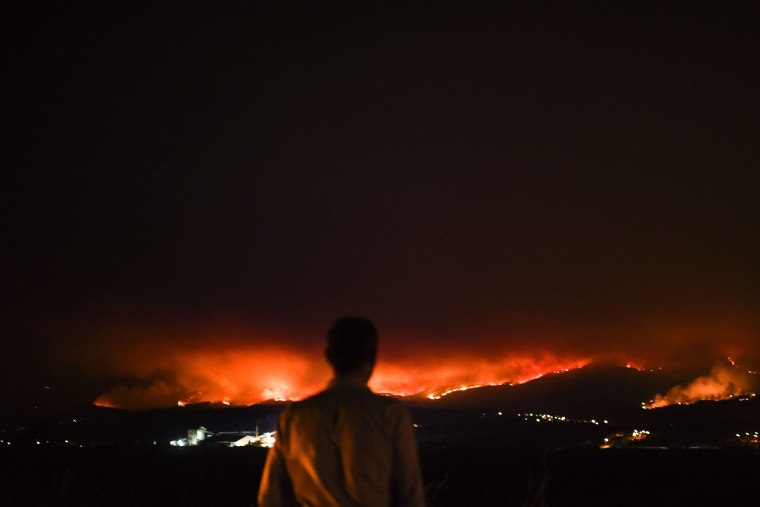 Image: A man stands on the roadside and watches the wildfire at Anciao, Leiria, central Portugal, on June 18.