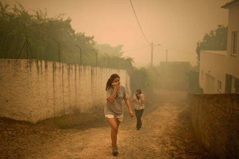 Image: Two people cover their mouths and noses with a tissue while fleeing the wildfire threatening the village of Torgal on June 18.