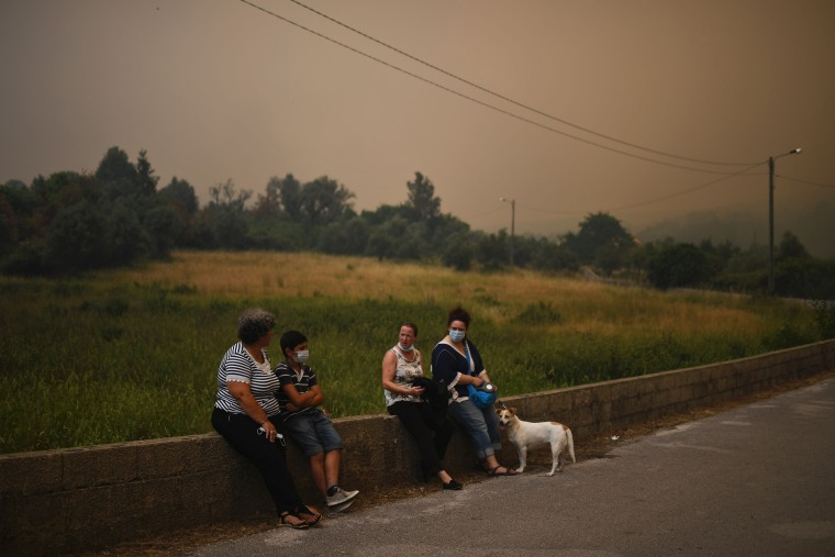 Image: Local residents, some with mask on their face, wait out the wildfire near Torgal on June 18.