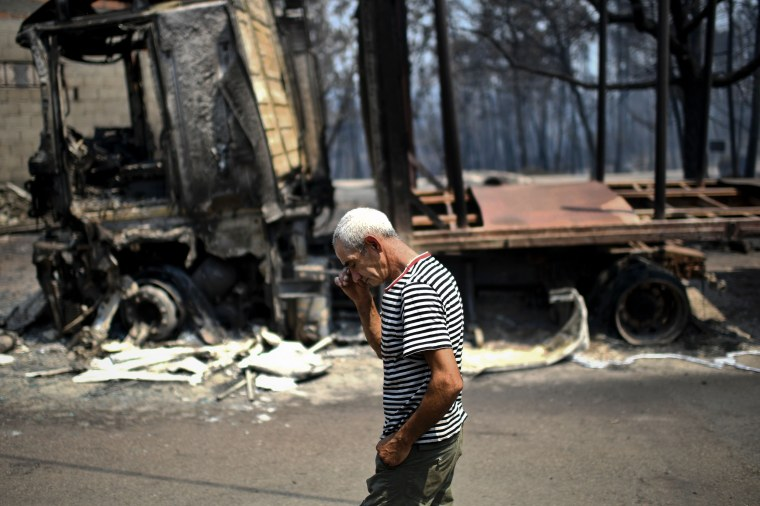 Image: A man passes by his burnt truck in Figueiro dos Vinhos on June 18.