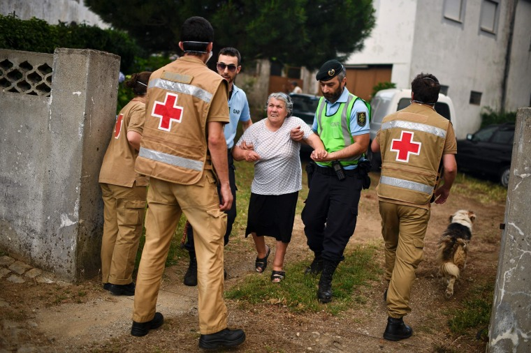 Image: People are evacuated from their houses by Red Cross and police members due the proximity of the dangerous wildfire at Torgal, Castanheira de Pera on June 18.