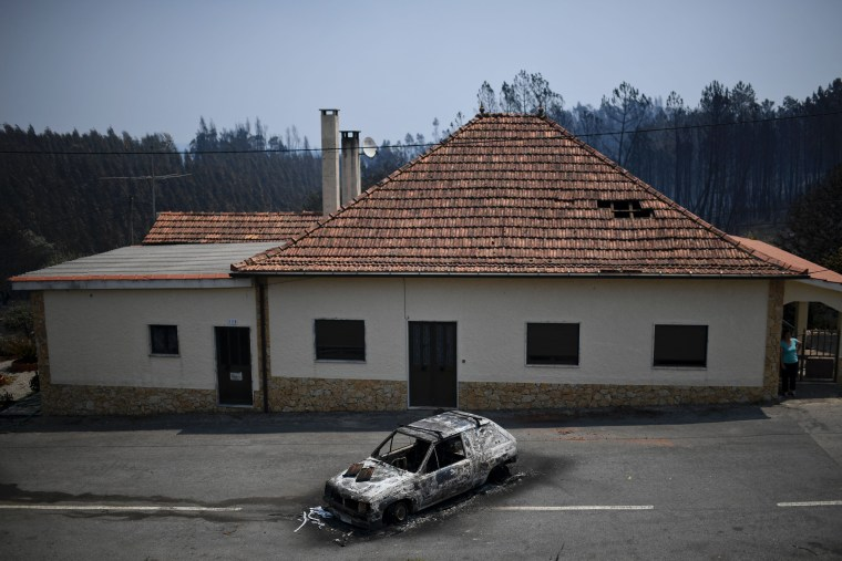 Image: A burnt car rests in front of a house after its brush with the wildfire in Figueiro dos Vinhos, June 18.