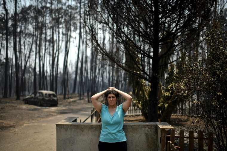 Image: Anabela Silva stands in front of her house with her burnt car in the background after a wildfire has swept through Figueiro dos Vinhos on June 18, 2017.