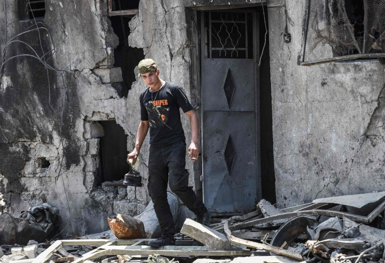 Image: A member of the Iraqi forces leaves a damaged building carrying a kettle