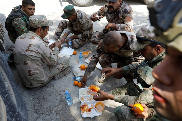 Image: Iraqi soldiers eat their meal along the road beside their armoured fighting vehicles in western Mosul