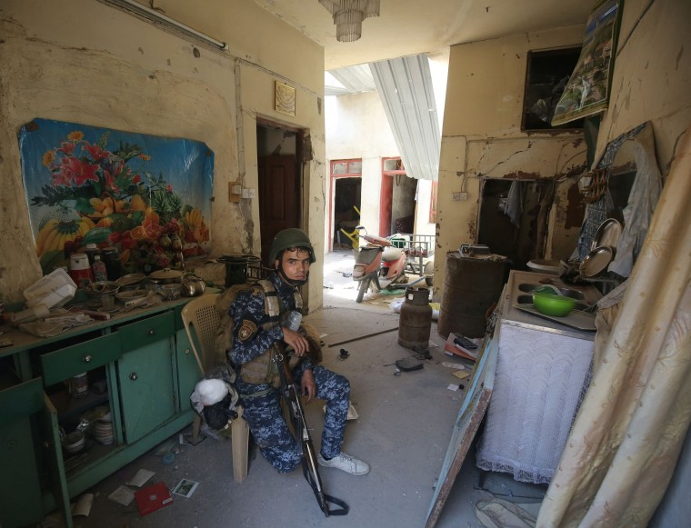 Image: A member of the Iraqi forces rests inside a house