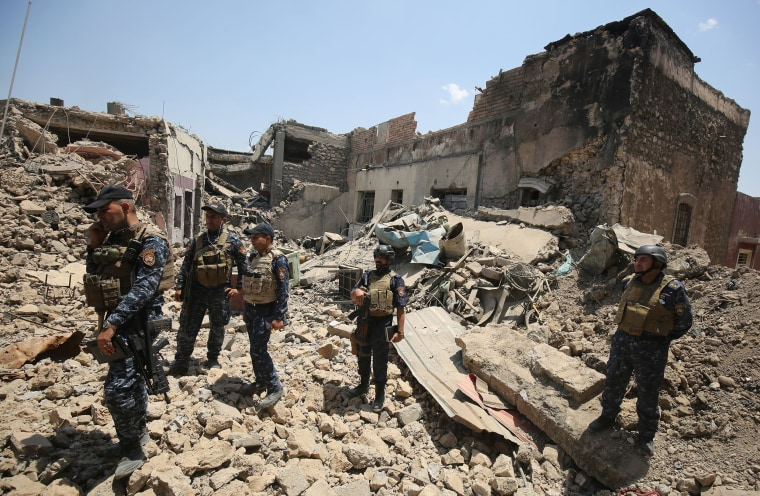 Image: Iraqi forces stand amidst the rubble of a building as they advance towards Mosul's Old City