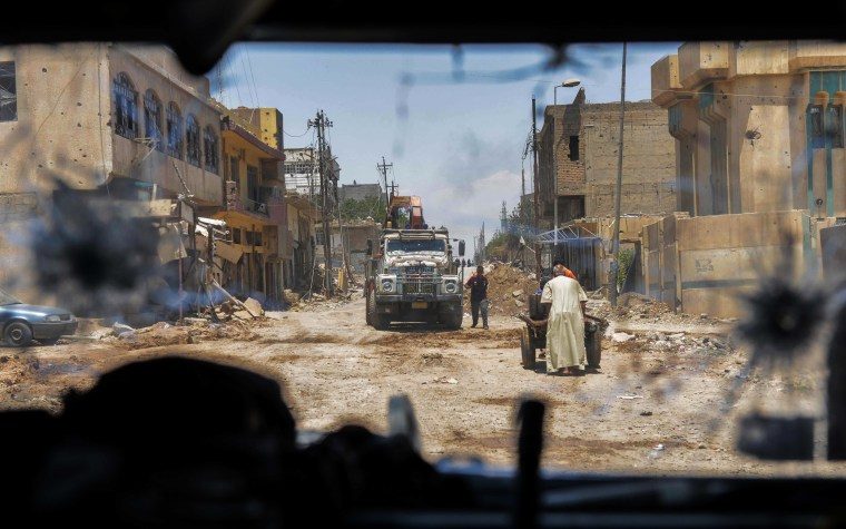 Image:  residents walking through a damaged street as troops advance towards Mosul's Old City