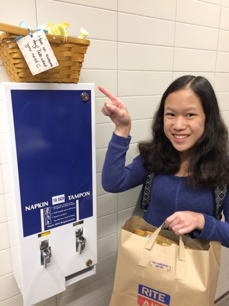 Cordelia Longo pointing to a sanitary napkin and tampon dispenser, on top of which is one of the baskets that she filled with free tampons and pads for the girls' restroom at Islander Middle School.