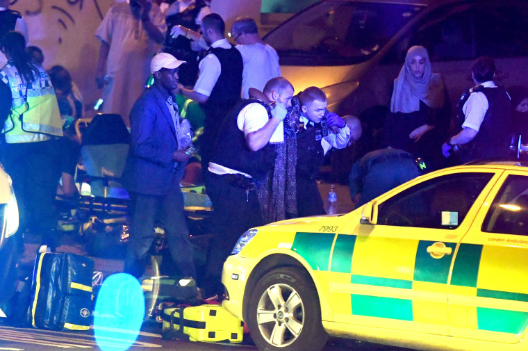 Image: Police and ambulance crews assist an injured pedestrian at the scene of the attack near Finsbury Park