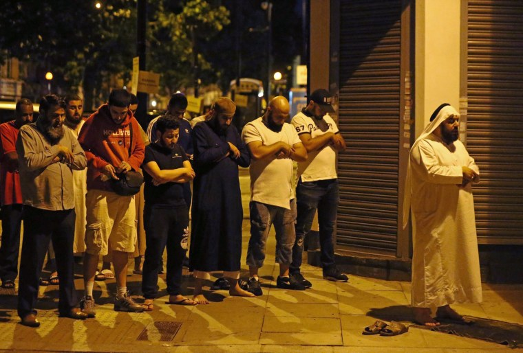 Image: Men pray after a vehicle collided with pedestrians near a mosque in the Finsbury Park neighborhood of North London