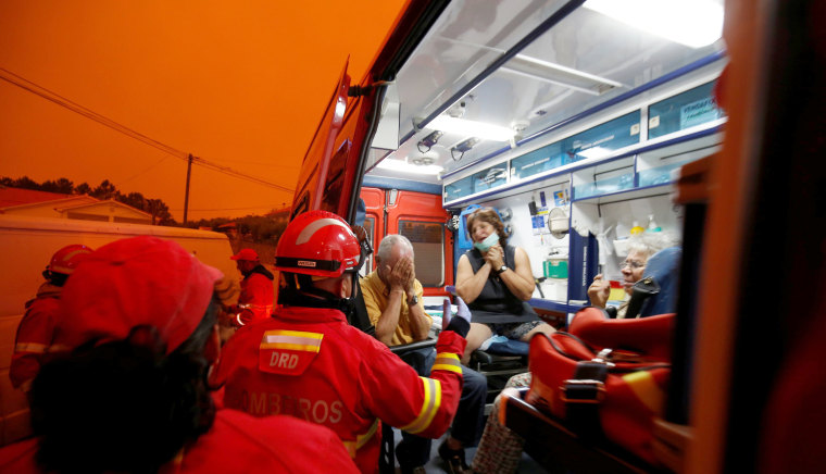 Image: Local residents are evacuated from the village of Derreada Cimeira on June 18.