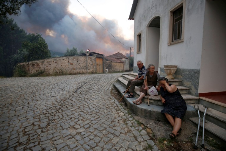 Image: Villagers sit outdoors as the fire burns near the village of Fato in central Portugal on June 18.