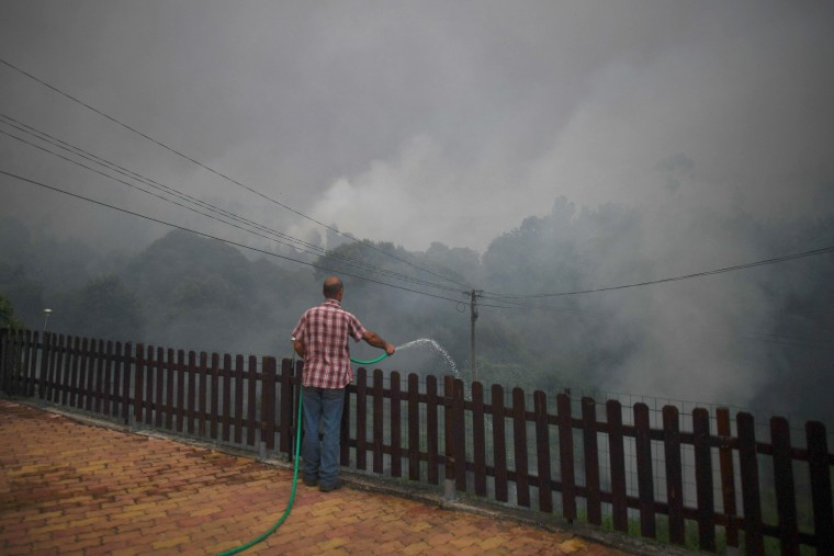 Image: A resident of the village of Trespostos uses a hose as he tries to extinguish the wildfire surrounding houses in Figueiro dos Vinhos on June 18.
