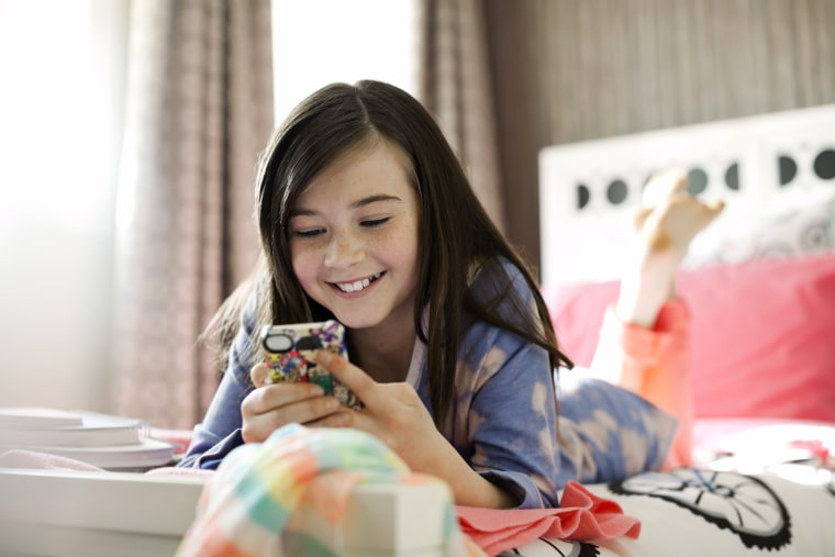 Image: Smiling Girl Using Smart Phone in Bed