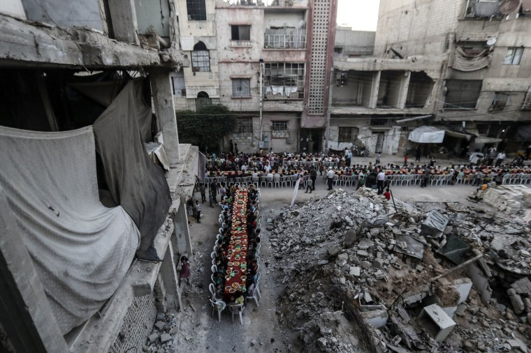 Image: People wait for Iftar, evening meal at the end of daily Ramadan fast at sunset, next to rubble and destroyed houses in Douma