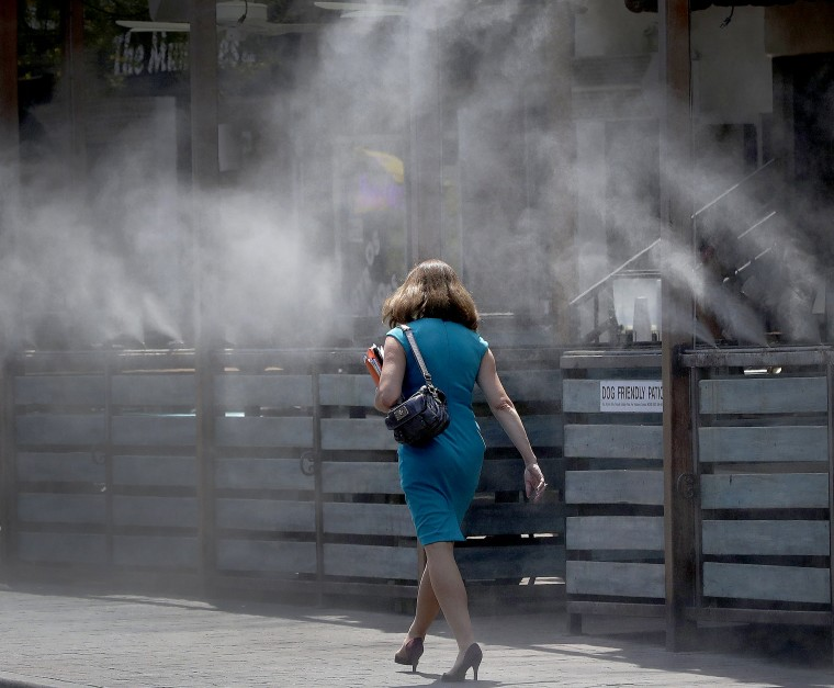 Image: A woman walks along a row of misters
