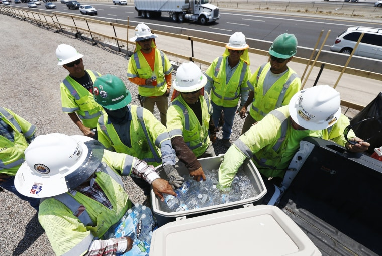 Image: Crew members building the Loop 202 South Mountain Freeway take a break as they try to keep hydrated and stay cool