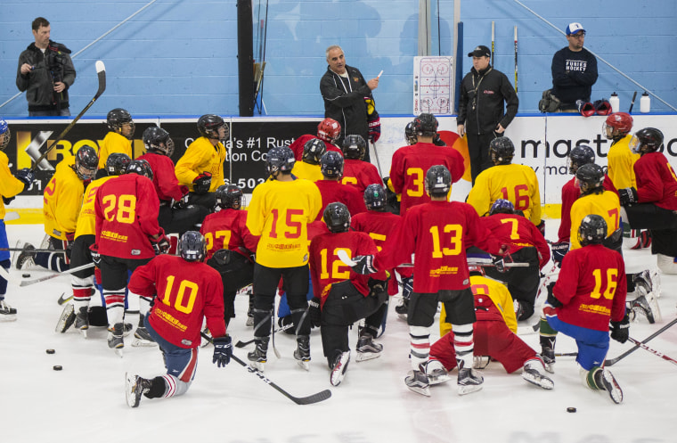 Players kneel on the ice as they listen to a coach during a training camp hosted by China's national hockey team.