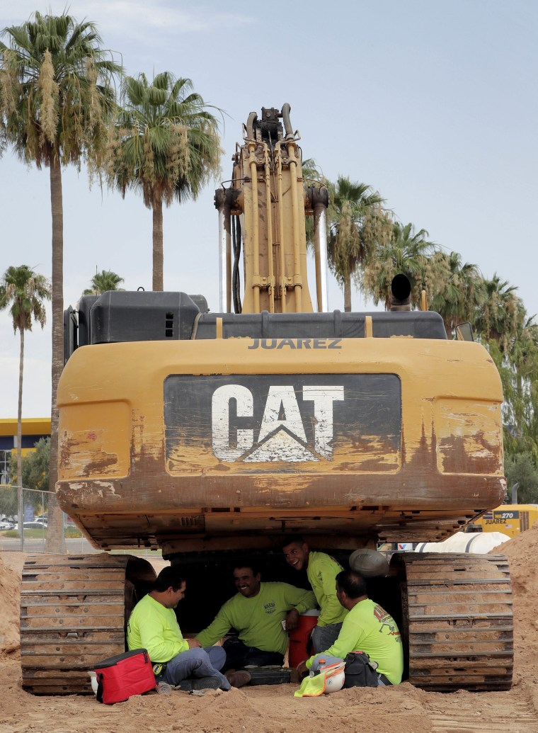 Image: A crew from Juarez Construction sits under their excavator during a break to avoid the heat