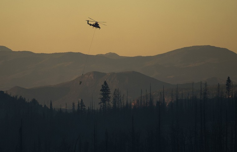Image: Helicopter crews put out hot spots as night falls in Utah