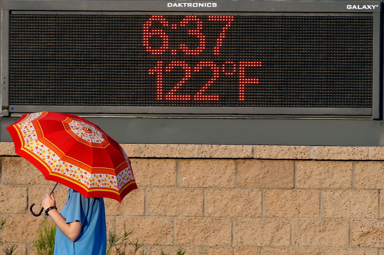 Image: A pedestrian uses an umbrella to shield herself from the sun