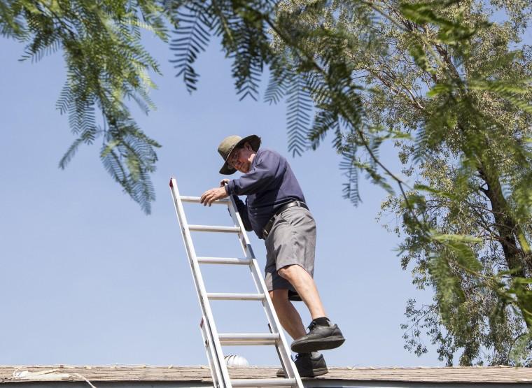 Image: An air conditioning repairman climbs down a ladder