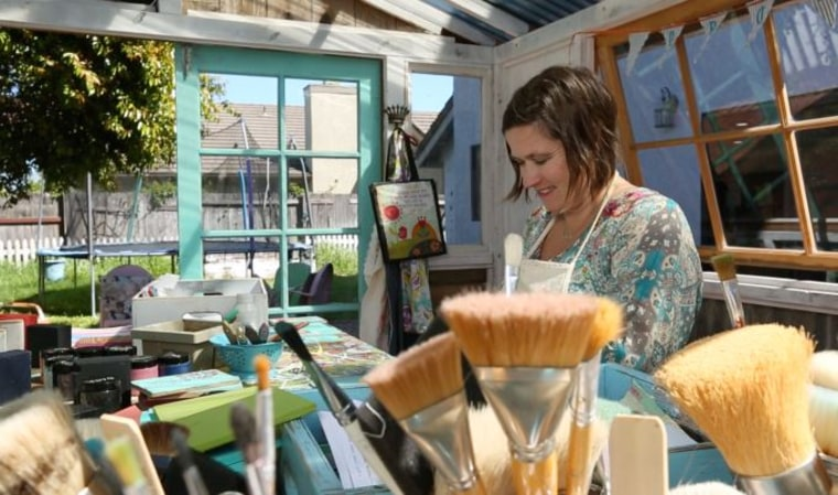 """Jenny Karp paints wooden greeting cards for her small business, Glitterfarm, in her """"She Shed"""" in San Luis Obispo, California."""