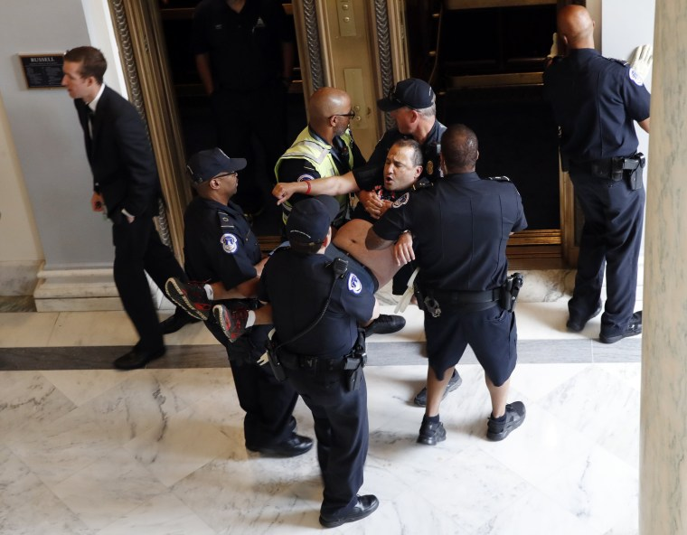 Image: A man is removed from a sit-in outside of Senate Majority Leader Mitch McConnell