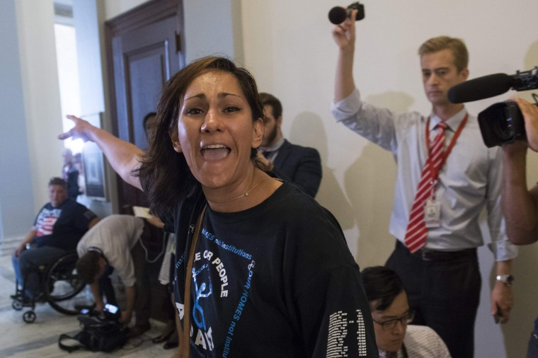 Image: A protester against the Senate Republican's draft healthcare bill shouts outside the office McConnell's office