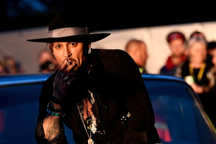 Image: Actor Johnny Depp poses on a Cadillac at Worthy Farm in Somerset during the Glastonbury Festival